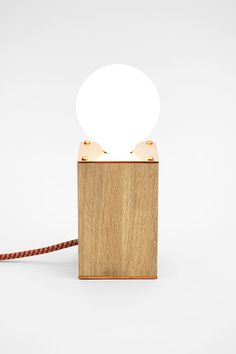 Simple and lovely bedside lamp in Scandinavian style - a dimmable light controlled by touch. Here shown in charming combination of brushed oak wood, rose gold copper and red, braided cord.