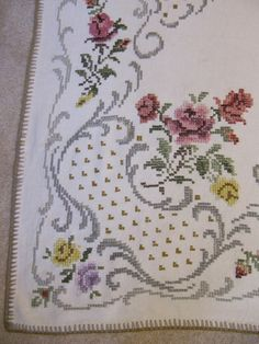 This table cloth was made by my grandmother-I have several and cannot keep all of them-in Germany some time in the 1920-1940s. It measures about 61 x 48 inches and is in excellent condition. The third photo shows a small gold colored spot next to the pink flower which is the only stain I see on it. I have not tried to clean it, it might come out I guess if I tried to spot clean it. It is heavy, substantial, gorgeous material-dont know if it is wool or linen, I dont think it is cotton. It has…