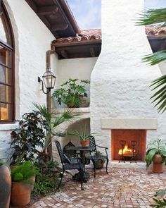This Spanish-influenced home features a brick patio and a large stucco outdoor fireplace.