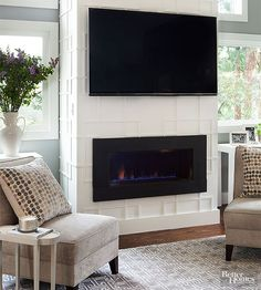 Style: Modern A simple white fireplace is accentuated with modern woodwork in overlapping square patterns. The sleek look is continued with a gas insert and TV hung just above the fireplace. The straight lines of the structure let the subtle woodwork shine and give the entire room a contemporary and chic feel./