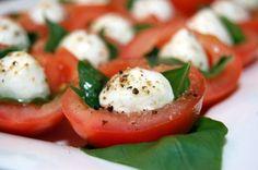 Tomaten gevuld met basilicum en mozzarella Bereidingswijzefoto's 1. Meng de olijfolie met flink wat versgemalen peper. Proef en voeg naar smaak meer toe. 2. Halveer de tomaten. Schep met een theelepel de zaadjes eruit en snij het kroontje weg. 3. Leg in elke helft een blaadje basilicum. Leg daar een mozzarellabolletje op. Besprenkel met een halve theelepel van de olijfolie. Serveer op kamertemperatuur.