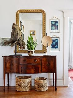 An antique burl-wood sideboard in the entry hallway is beautifully balanced by a Louis Philippe mirror, woven baskets, and original art.