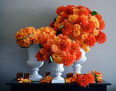 Brilliant orange flower arrangements in complementary blue vases. #orange #flowerarrangement #wedding