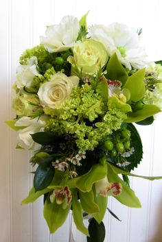 Cascade bouquet with green hydrangea, green cymbidium orchids, green and white roses, wax flower and anemones.