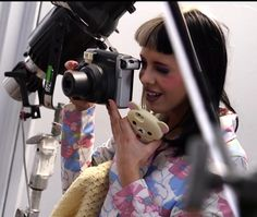 Melanie Martinez  taking a photo to her friend on her set of crybaby the music video
