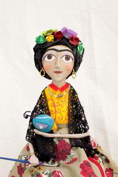 Sim! Nós temos Frida!! Nossa Frida é feita em Papel Machê, sucatas, tecidos e papeis variados. São bonecas únicas, pois fazemos as roupinhas diferentes umas das outras e variamos a posição da escultura. Ela possui aproximadamente 55 cm de altura.