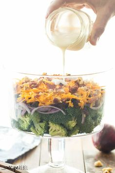 My husband's FAVORITE! This Layered Broccoli Salad is loaded with cheddar cheese, raisins, cranberries, bacon and served with a sweet & tangy dressing!