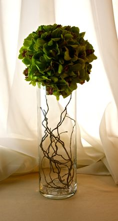 A sphere of Dendrobium Orchids sits atop a cylinder filled with Willow branches in a modern centerpiece or accent arrangement