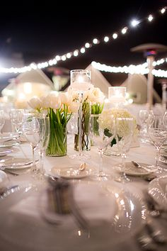All-white centerpieces of hydrangeas, tulips, freesia, garden roses, and dahlias | @cloveandkin | Brides.com