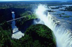 Cararatas Victoria. Cataratas Victoria tienen una altura de 108 metros y abarcan una longitud de 1,4 kilómetros en la frontera de Zambia y Zimbabue. La cantidad de agua que cae es exorbitante, de hecho, en los días claros, se puede ver la espuma de las cataratas a una distancia de casi 30 kilómetros.