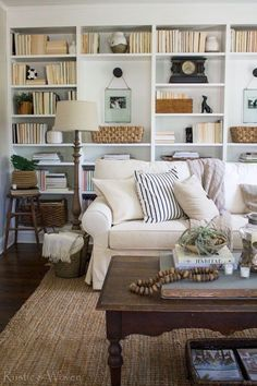 Rustic farmhouse living room decor in neutral colors with built-in bookcases, a white slipcovered sofa, rustic wood coffee table, and seagrass area rug - Farmhouse Decor & Decorating Ideas