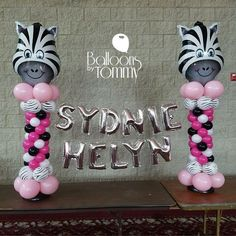 Animal themed baby shower with a pink, white, and black theme! Zebra printed balloons and a zebra head foil balloon work together for this fantastic centerpiece featuring the baby's name in foil balloon letters! | Balloons by Tommy | #balloonsbytommy