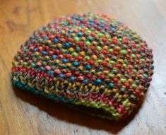 This adorable, tiny knit hat pattern is a beautiful burst of color for a little baby's head. The Wild Flower Preemie Hat is a bright, nubby knit hat that will cozily hug her head and ears.