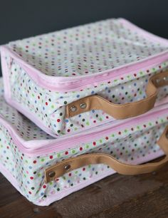 2 pretty play suitcases for children made from pretty paterned fabric.