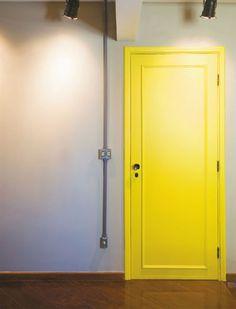 porta amarela com parede cinza Mais
