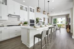 A clean white kitchen with up-to-the-ceiling cabinetry is grounded by the deeper wood-look flooring, weathered grey pendants over the island and taupe counter stools. Revo Plan One at Novel Park for William Lyon Homes Counter Stools, Design Awards, Home Office, Kitchen Design, Flooring, Inspiration, How To Plan, Interior Design