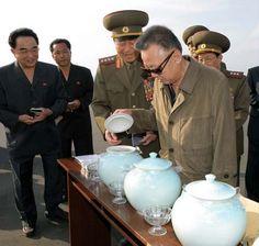 Kim Jong Il looking at a ceramic pot.