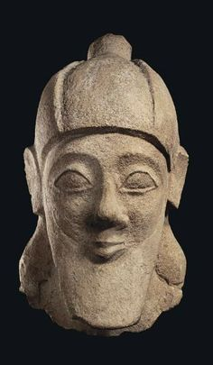 Cypriot limestone male head, early 6th century B.C.  Likely from a votary statue, wearing a conical helmet peaked at the crown, his face with sharp arching brows merging with the bridge of the pointed nose, the large almond-shaped eyes with thick lids, the small mouth with pursed lips, his hair falling behind his ears in a mass along his neck, and with a long spade-shaped beard, 26 cm high. Private collection