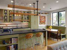 Green island accents & green cabinets set the earthy tone for this eclectic, vintage kitchen.