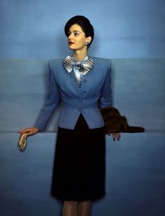 Model wearing two-tone blue and brown Cohama wool suit,1944. color photo print ad model magazine vintage fashion style blue suit jacket black pencil skirt bow blouse hat gloves mid 40s padded shoulders peplum