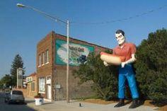 Image copyright                  Alamy Image caption                                      La estatua gigante dedicada al legendario leñador Paul Bunyan que sostiene entre manos un perrito caliente igual de colosal anuncia un café en la famosa Ruta 66, en Illinois, EE.UU.                                Quien salga de viaje por las carreteras de Estados Unidos tarde o temprano se topará con una estatua gigante, tal vez de un vaquero, un jefe