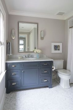 Navy cabinet paint color is Benjamin Moore French Beret 1610. Wall paint color is Farrow and Ball Cornforth White 228. Floors are 1″ Circle Polished White Statuary Calacatta Marble. Martha O'Hara Interiors.