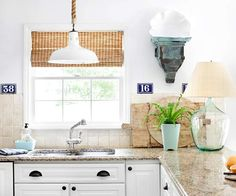 Rope pendant light, countertops, white cabinets, black pulls