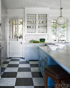 """In the conservatory, milk-glass skylights and picture-window walls flood the room with sunlight. The spacious kitchen is period correct, with a Dutch door, Marmoleum patterned to resemble the marble checkerboard of a dance floor, and a paint color that morphs from blue to gray to pale green. """"It's not a white kitchen,"""" Stuart declares. """"If I see one more of those, I will hang myself."""" The kitchen counters are quartzite, the cabinetry is custom made, and the flooring is Marmoleum…"""