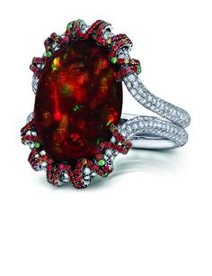 Cabochon fire opal, 13.18 carats; surrounded by 354 diamonds, 14 green tsavorite garnets and 179 orange-red sapphires. Micro-set diamond double band in 18K white gold setting.