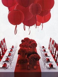 Red paper lanterns with ribbon streamers above a crimson table runner with same-bloom cluster arrangements and candles.