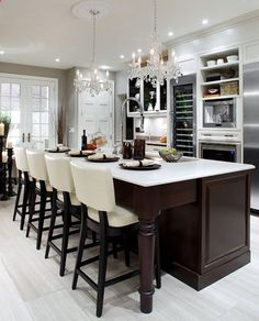elegant kitchen design with cream leather barstools, double crystal chandeliers, chocolate brown stained kitchen island, white quartz counter tops, white kitchen cabinets and soft gray paint color.