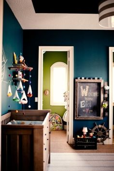 Dark blue and line green nursery with antique changing table. Cute mobile.  Lose the chalkboard and old blocks