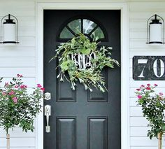 entryway with white siding, pink roses, black door, silver hardware, white lanterns, green wreath, metal house numbers thistlewoodfarms.com