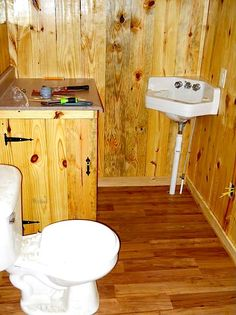 Note the cabinet door next to the toilet. It's access to the hot water heater. But this if a good ideal for toilet paper, etc. storage as well. How to Build a Mortgage-free Small House for $5,900