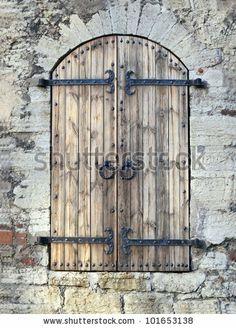 Antique wooden door with iron hinges and old metal handles by Marek Mix, via Shutterstock