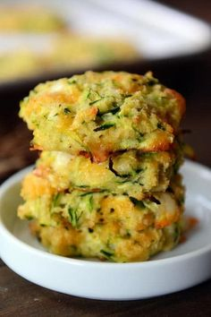 Four Baked Cheesy Zucchini Bites stacked on a white ramekin.