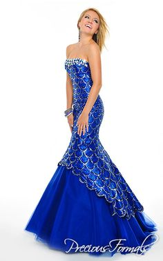 Precious Formals Style O55173 This long mermaid style dress has an overlay of taffeta with patterns of glitter scales and jewels bordering the strapless bodice while letting layers of illusion peek out from the bottom.