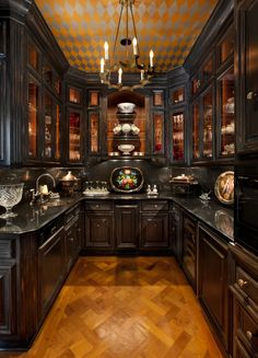 Butlers pantry and bar with glass-front cabinetry, granite counters, microwave, warming drawer, refrigerator, wine cooler, dishwasher, and ice maker.  #chandeliers  #miele