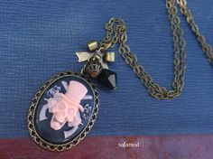 Gothic spirit, pretty necklace with bronze backing, resin skull cap gun black pink roses, ribbon bow, round filigree beads, pearl top, all mounted on bronze chain. Clasp.