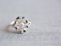 A gorgeous antique ring with a central old European Cut diamond and diamond spokes that swirl out into a sapphire halo! How unique!