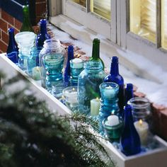 For a striking display cluster colored and clear glass bottles, jars, and vintage insulation glass in an outdoor window box. Vary heights, shapes, and colors for visual interest. Insert votives or flickering battery-operated candles Christmas Window Boxes, Winter Window Boxes, Christmas Window Decorations, Bottle Decorations, Outdoor Decorations, Indoor Window Boxes, Window Sill, Room Window, Bougie Candle