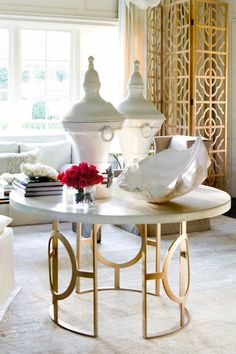 Chic living rom with gold quatrefoil floor screen, milk chocolate slipcover wingback chair and marble top antique fretwork table.