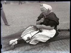 Vrouw bezig met netten boeten in Scheveningen, ongeveer 1950-1955. Woman in traditional costume mending fishing nets in Scheveningen, the Netherlands, around 1950-1955