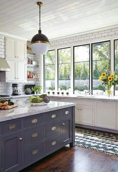 Blue island and statement lighting with metro tiles in the kitchen