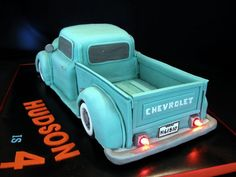 """The open bed is on 1"""" layer of RKT covered in fondant. The bed sides and tail gate are gumpaste. The fenders are RKT. The tires are gumpaste."""