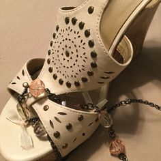 Cute Summer Sandals! Cream colored stencil cut sandals with studs. Cork faced heel with small platform. Very cute with everything summery. One leather loop is slightly worn as shown in third picture. And one stud is missing as shown in cover picture. Price reflects defects ... no one will notice when you are wearing them - good for at least a couple more summers. Charlotte Russe Shoes Heels