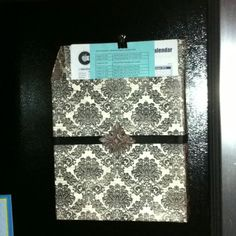 cereal box and covered it with scrapbook paper.  glued large, round magnets on the back, attached a ribbon