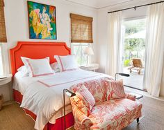 This coral bedroom is perfectly polished. The upholstered bed with matching bedskirt, embroidered linens, and print on the settee are beautiful