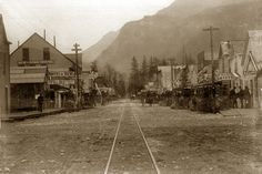 White Pass and Yukon Railroad, Alaska   Broadway Street, Skagway with WP & Y Railroad tracks running length of street  The Pillbox Drug Co., Photos & Views, Burkhard House, Headquarters Yukon Outfitters, Dyea Mercantile  Harry C. Barley photo  After June 15, 1898