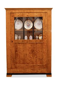 A Biedermeier book cabinet    German, early 19th cent. Flammed birch veneered and with ebonised accent. One-door cabinet, the top part glass-in. Rest., add. H. 179 cm, w. 123 cm, d. 40 cm.